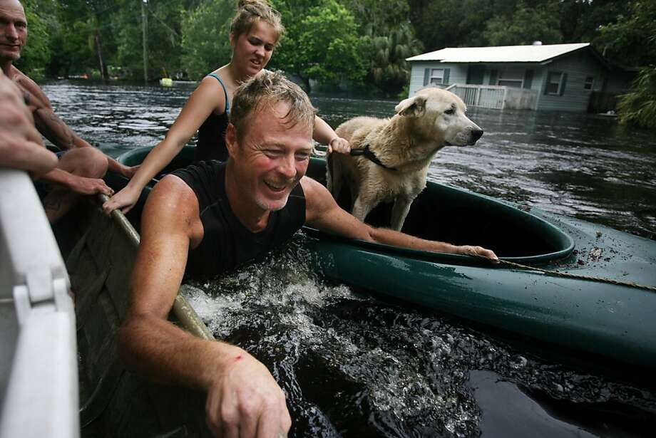 Richard Williams, left, rescues his neighbors, Marty Hieftje, left, Hieftje's 16-year-old daughter Katelyn Hieftje and the Hieftje's dog Delilah after they became stranded Tuesday, June 26, 2012, in Elfers, Fla, at their home on Elfers Parkway, at right, where the Anclote river left its banks flooding dozens of homes, a result of tropical Storm Debby.  (AP Photo/Tampa Bay Times, Douglas R. Clifford) Photo: Douglas R. Clifford, Associated Press