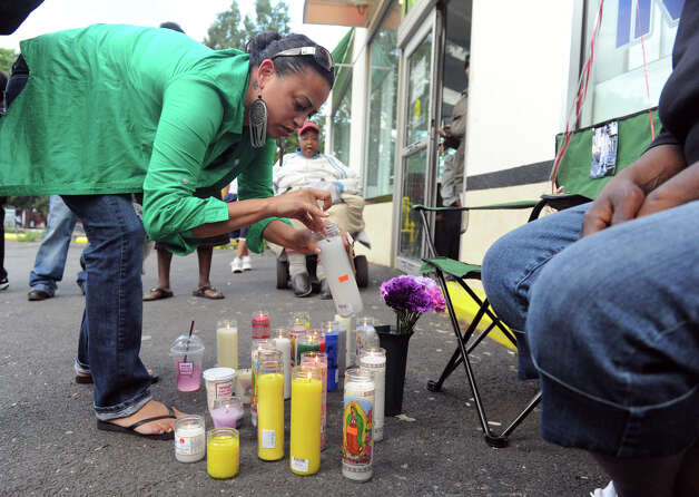 Lizmarie Vasquez lights a candle in memory of homicide victim Jimmy Decrescenzo as his friends gather to remember him outside Uncle Buck's Laundromat on Stillwater Avenue, where he was killed after an apparent robbery in Stamford, Conn., June 26, 2012. Photo: Keelin Daly / Stamford Advocate