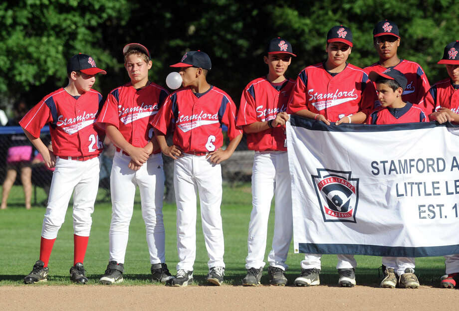 Chris Rojas, center, blows bubbles as he and teammates from the Stamford American Little League team attend the Little League Opening Ceremonies at Springdale's Drotor Field in Stamford, Conn., June 26, 2012. Photo: Keelin Daly / Stamford Advocate
