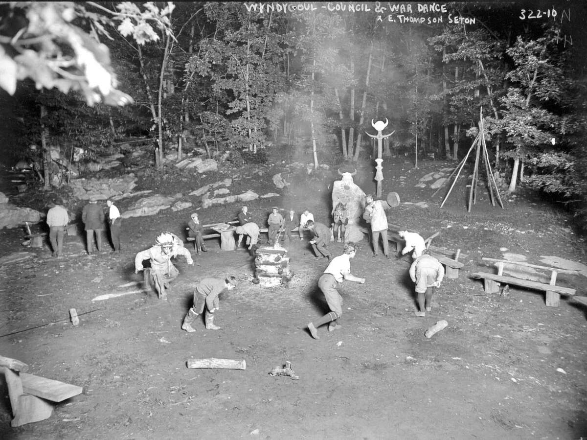 """In this photo, circa 1905, Ernest Thompson Seton's Woodcraft Indians perform a council and war dance at a campground at Seton's Wyndygoul estate in Cos Cob. Note Seton beating a """"tomtom"""" beside an unusual stone monument that was known as Medicine Rock."""