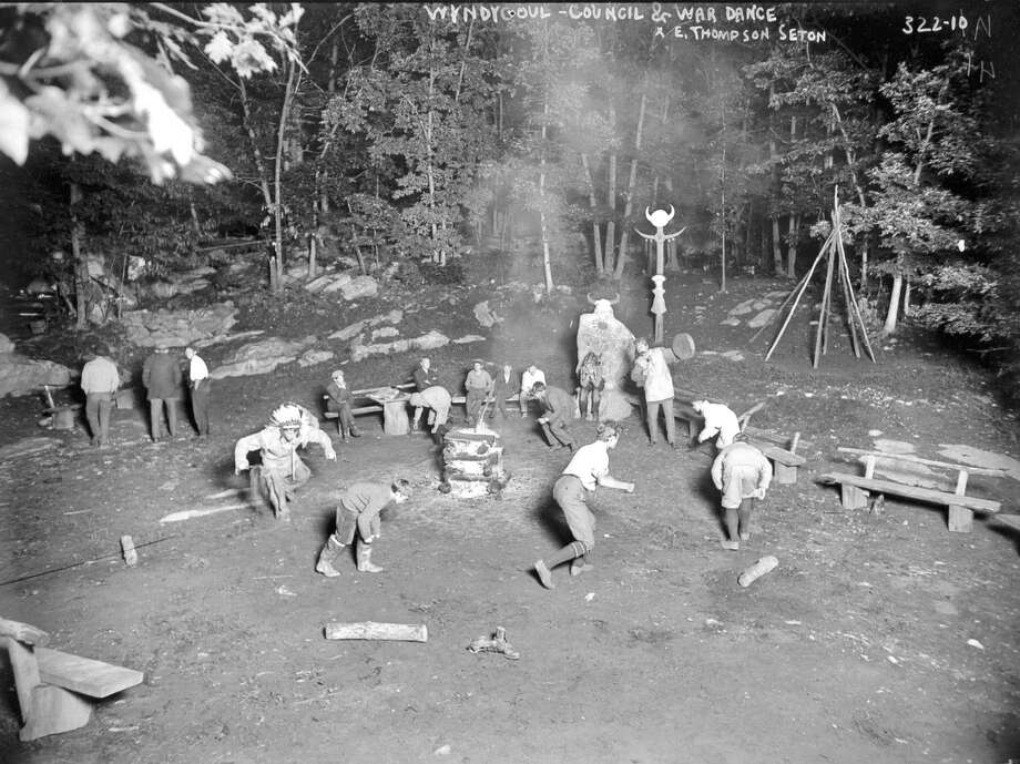 "In this photo, circa 1905, Ernest Thompson Seton's Woodcraft Indians perform a council and war dance at a campground at Seton's Wyndygoul estate in Cos Cob. Note Seton beating a ""tomtom"" beside an unusual stone monument that was known as Medicine Rock. Photo: Contributed Photo"