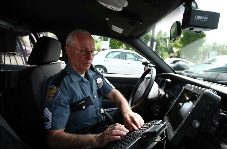 Seattle Police Sergeant Major Arny McGinnis works on his computer while patrolling Rainier Avenue South on Wednesday, June 20, 2012. McGinnis, 74, said younger officers were helpful in helping him master his computer and many of the other devices used by a modern officer. McGinnis is retiring from the Seattle Police Department after working as a patrol officer for 50 years. He was recently given the title of Sergeant Major. Photo: JOSHUA TRUJILLO / SEATTLEPI.COM