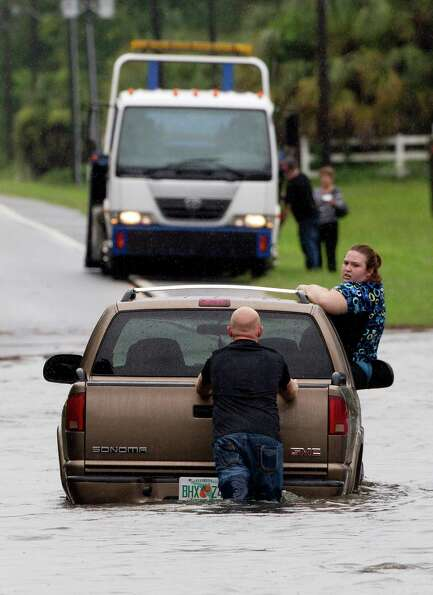 A motorist pushes his car through deep flood water near Live Oak Fla., Tuesday, June 26, 2012.  Floo