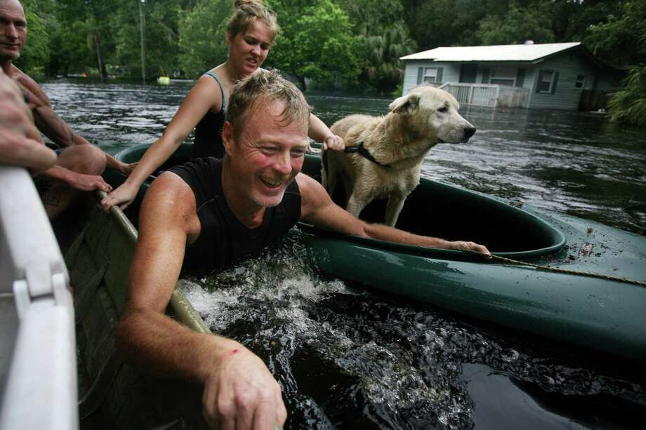 TROPICAL STORM DEBBY: The storm made landfall at Steinhatchee, Fla., on June 26, then lost most of its steam quickly. But it crossed Florida, dumping lots of rain. Above, Richard Williams, left, rescues his neighbors after they became stranded June 26, 2012, in Elfers, Fla.  Photo: Douglas R. Clifford, Associated Press / Tampa Bay Times