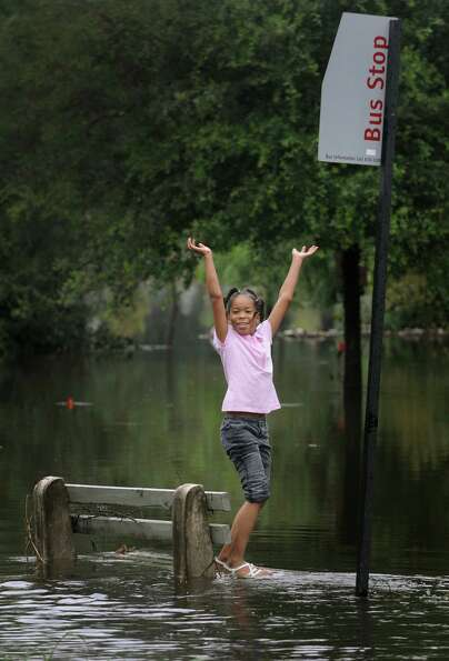 Journey Wooten, 8, stands on the base of a bench that is submerged in Jacksonville, Fla.  Tuesday, J