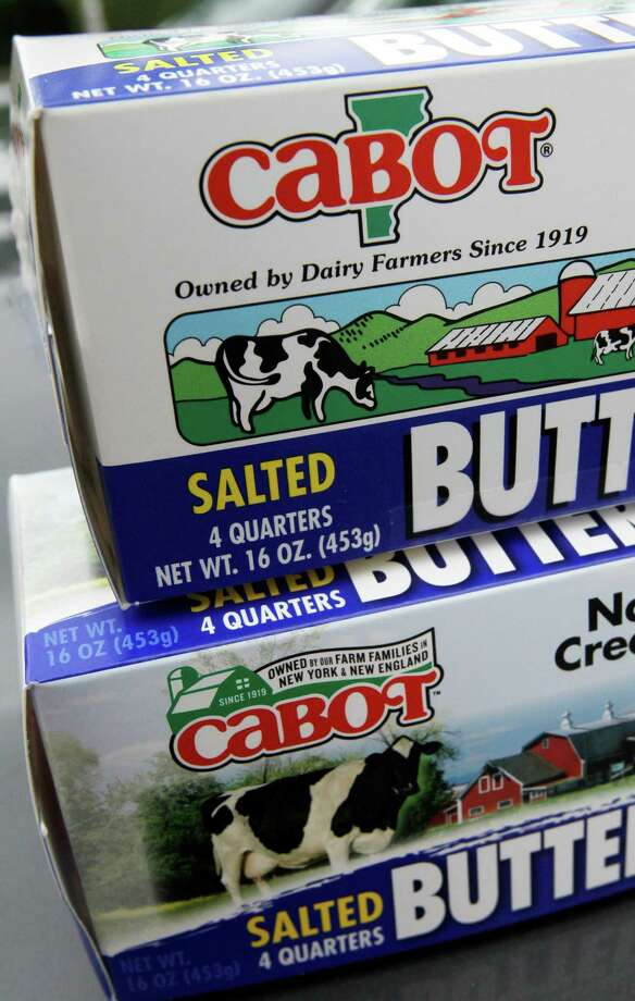 """The old Cabot logo, top, and the new logo, bottom, are displayed on packages of butter on Tuesday, June 26, 2012 in Waterbury, Vt. Cabot Creamery Cooperative, maker of cheese, butter and other dairy products, is phasing out labels with the state on the logo. A green outline of the state is being dropped in favor of a green barn and the words """"Owned by our Farm Families in New York & New England.""""(AP Photo/Toby Talbot) Photo: Toby Talbot"""