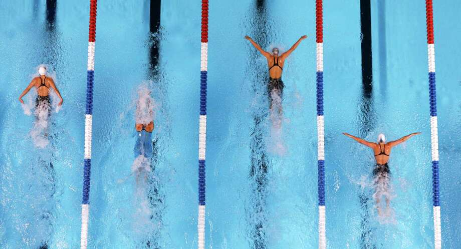 Natalie Coughlin, from left, Elaine Breeden, Dana Vollmer and Kathleen Hersey compete in the women's 100-meter butterfly final at the U.S. Olympic swimming trials, Tuesday, June 26, 2012, in Omaha, Neb. Voollmer won the race. Photo: Mark Humphrey, Associated Press / AP