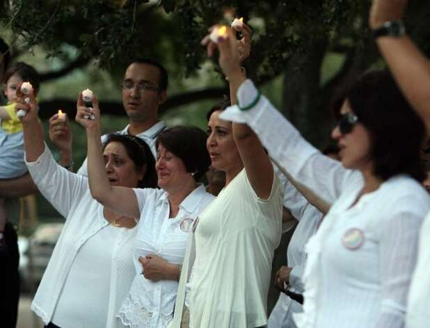 Gelareh Bagherzadeh's mother, Monireh Zangeneh, second from left, cries at the vigil for her daughter at the Williams Waterwall on Post Oak on June 26. (James Nielsen / Chronicle)