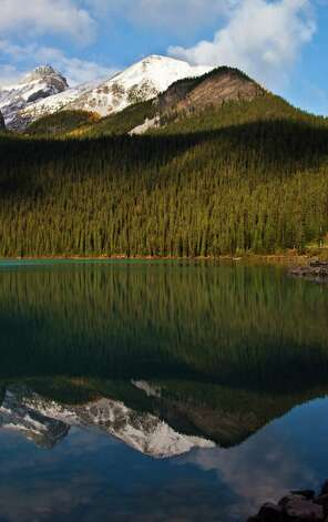 The Canadian Rockies are reflected in the glassy surface of Lake Louise. Photo: Joshua Trudell, For The Express-News
