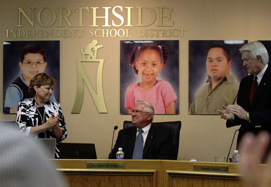 Northside Independent School District board members Randy Fields (right) and Karen Freeman (left) join others in applauding outgoing superintendent Dr. John M. Folks (center) on his last day to attend a board meeting for the district on Tuesday, June 26, 2012. Folks has served as superintendent for NISD for nearly a decade before announcing his retirement back in December 2011. Photo: Kin Man Hui, San Antonio Express-News / ©2012 San Antonio Express-News