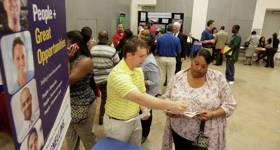 Travis Sowa, left, a business development manager with Snellling Staffing, talks with Alondra White on Tuesday during a job fair for ex-offenders at the Houston Food Bank. Photo: Melissa Phillip / © 2012 Houston Chronicle