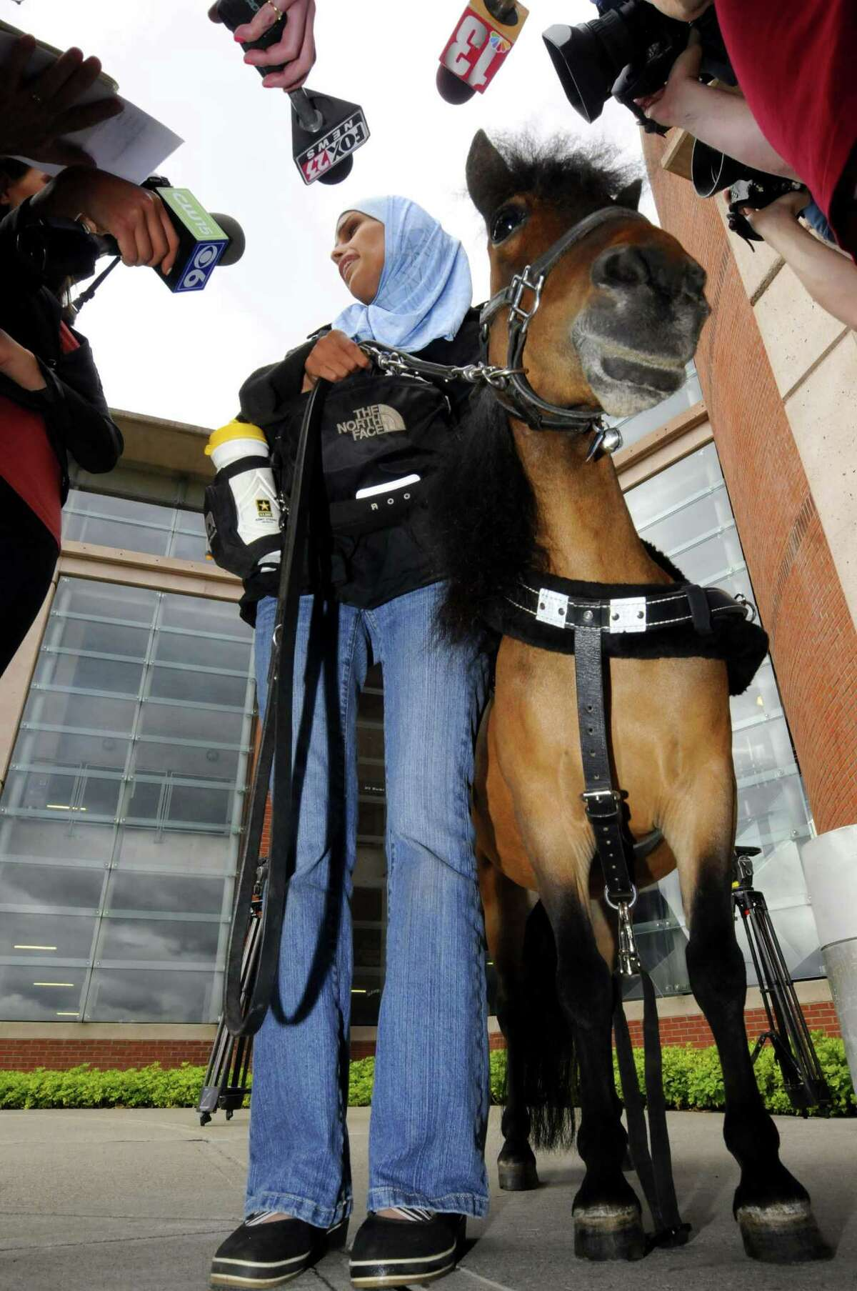 Mona Ramouni, who is blind, talks with local media following her at Albany International Airport with Cali her guide horse in Colonie N.Y. Tuesday June 26, 2012. (Michael P. Farrell/Times Union)