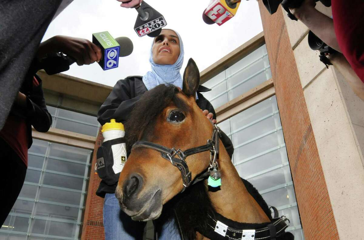 Mona Ramouni, who is blind, talks with local media following her arrival at Albany International Airport with Cali her guide horse in Latham N.Y. Tuesday June 26, 2012. (Michael P. Farrell/Times Union)