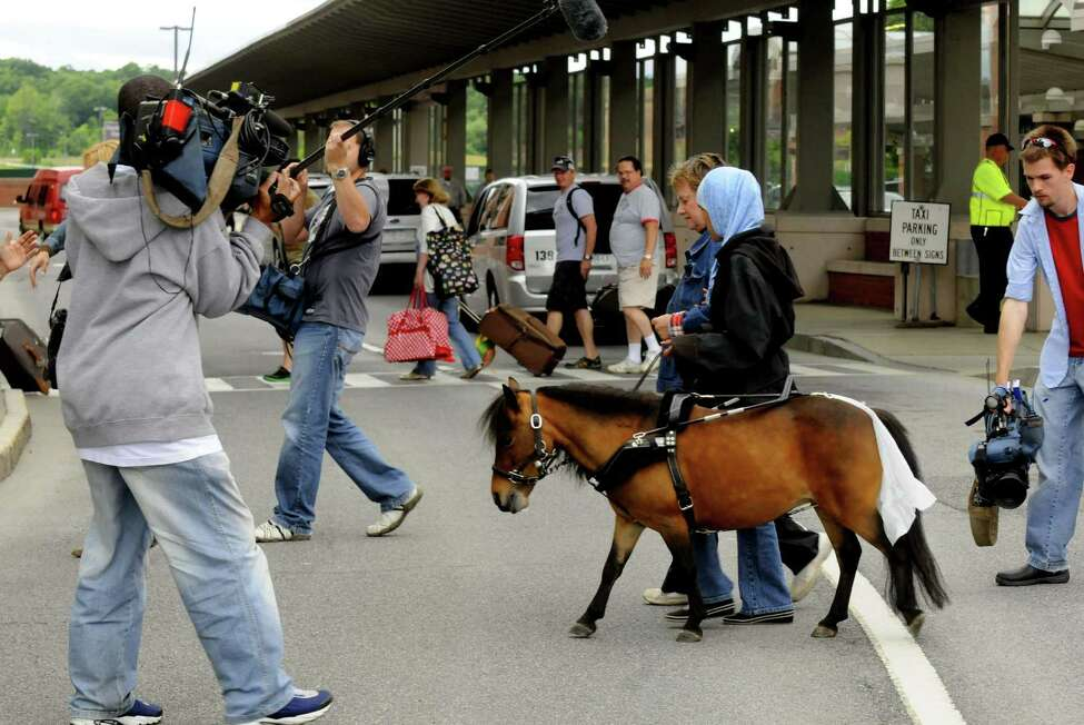 Followed by local media and an Australian film crew Mona Ramouni, who is blind, talks local guide horse trainer Dolores Arste of Galway following her arrival at Albany International Airport with Cali her guide horse in Latham N.Y. Tuesday June 26, 2012. (Michael P. Farrell/Times Union)