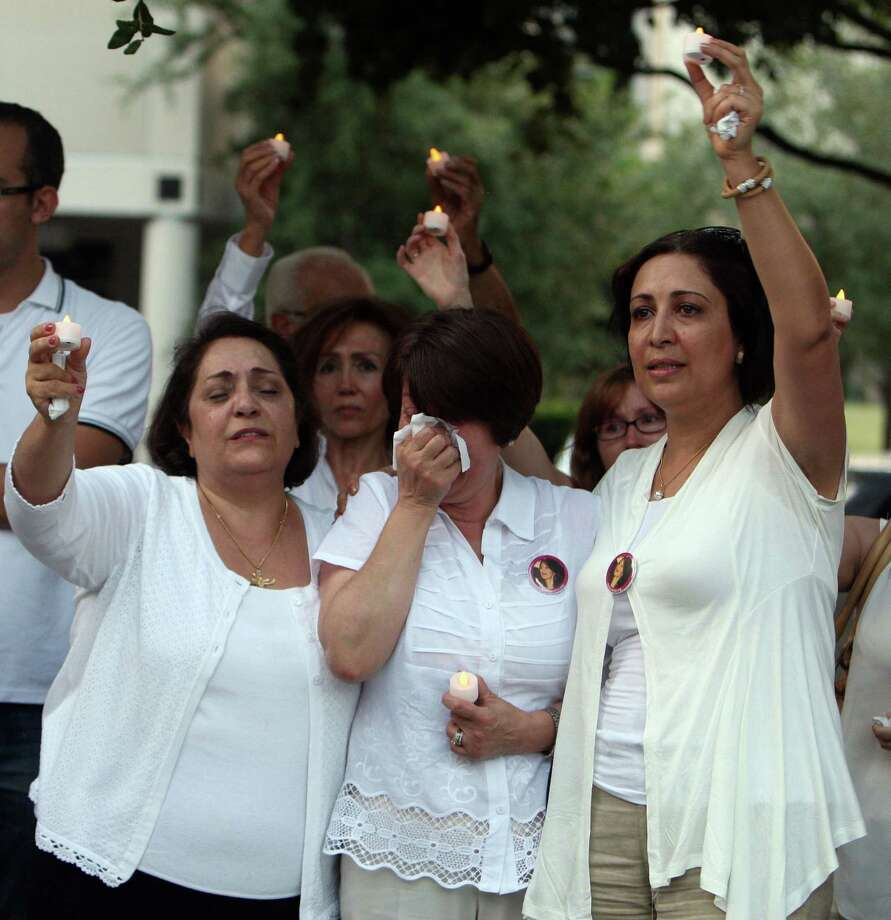 "Monireh Zangeneh, center, Gelareh Bagherzadeh's mother, cries during a candlelight vigil Tuesday to commemorate Bagherzadeh's 31st birthday as Fatemeh Jameson left, and Kathy Soltani sing ""Happy Birthday"" at the Gerald D. Hines Waterwall Park. Photo: James Nielsen / © Houston Chronicle 2012"