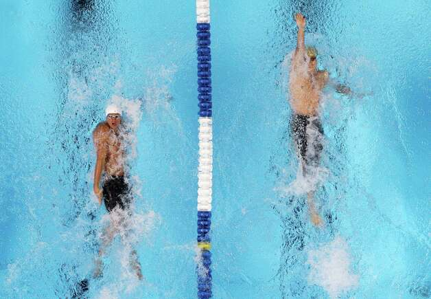 Ryan Lochte, left, and Nick Thoman swim in the men's 100-meter backstroke preliminaries at the U.S. Olympic swimming trials, Tuesday, June 26, 2012, in Omaha, Neb. (AP Photo/Mark Humphrey) Photo: Associated Press