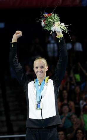 Dana Vollmer celebrates during the medal ceremony after winning the women's 100-meter butterfly final at the U.S. Olympic swimming trials, Tuesday, June 26, 2012, in Omaha, Neb. (AP Photo/David J. Phillip) Photo: Associated Press