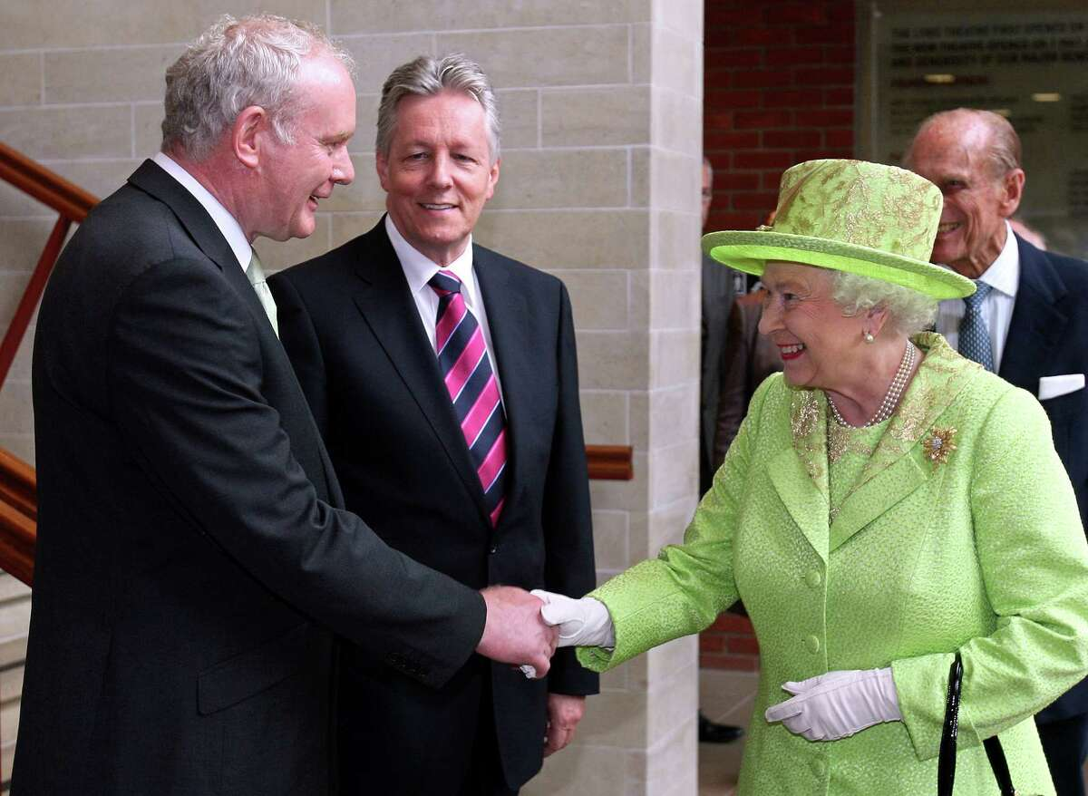 Britain's Queen Elizabeth II (2nd R) shakes hands with Northern Ireland Deputy First Minister Martin McGuinness (L) watched by First Minister Peter Robinson (2nd L) and Prince Philip (R) at the Lyric Theatre in Belfast, Northern Ireland, on June 27, 2012. Queen Elizabeth II shook hands with former IRA commander Martin McGuinness on Wednesday in a landmark moment in the Northern Ireland peace process, Buckingham Palace said. The initial handshake between the queen and McGuinness, who is now deputy first minister of the British province, took place away from the media spotlight behind closed doors in Belfast's Lyric theatre. AFP PHOTO / PAUL FAITH/POOLPAUL FAITH/AFP/GettyImages