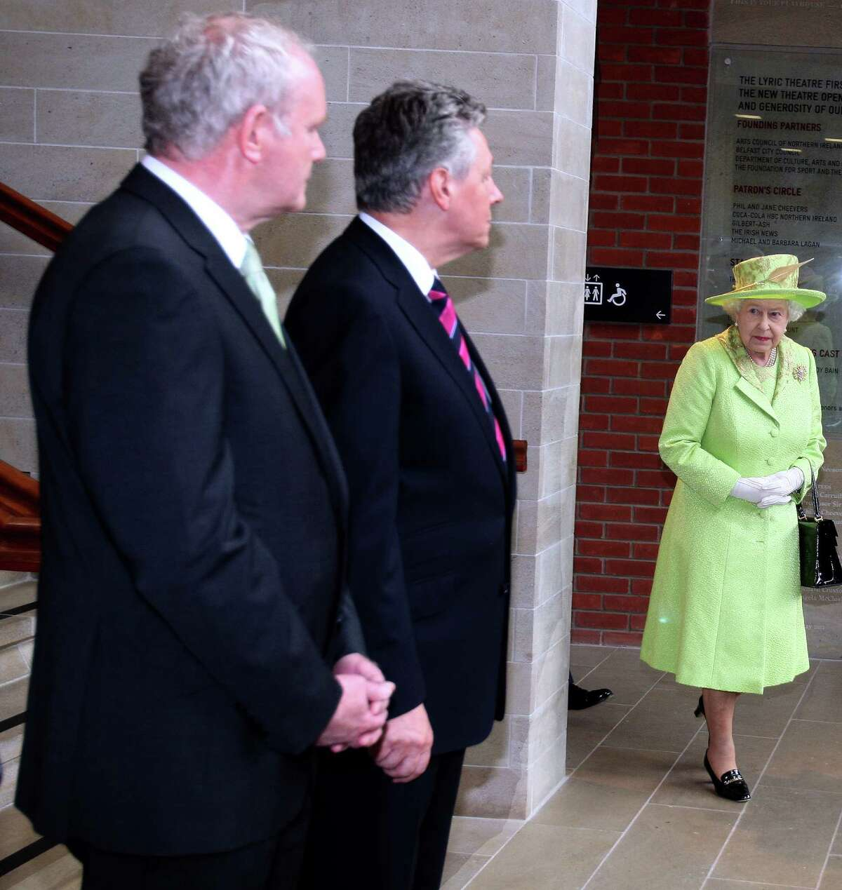 BELFAST, NORTHERN IRELAND - JUNE 27: Queen Elizabeth II arrives to meet with Deputy First Minister of Northern Ireland Martin McGuinness (L) and First Minister Peter Robinson (C) at the Lyric Theatre on June 27, 2012 in Belfast, Northern Ireland. During the Queen's two day visit to Northern Ireland she held a hugely significant meeting with former IRA commander and deputy First Minister of Northern Ireland, Martin McGuinness at the Lyric Theatre today. The Queen will also visit the newly opened Titanic Museum and the town of Enniskillen.