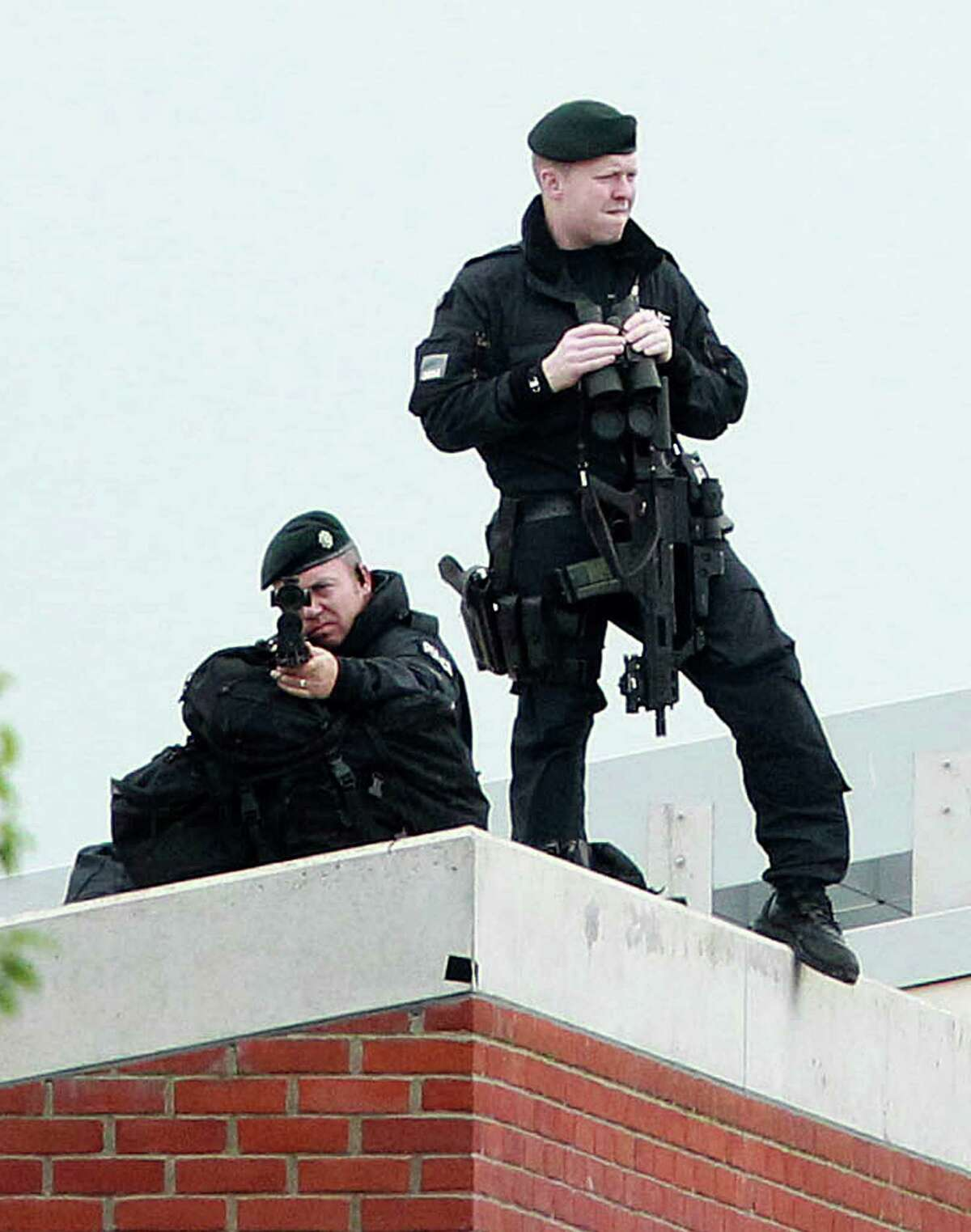 Armed police keep watch from the roof of the Lyric Theatre in Belfast, Northern Ireland, on June 27, 2012, as Britain's Queen Elizabeth II shook hands with Northern Ireland Deputy First Minister Martin McGuinness. Queen Elizabeth II shook hands with former IRA commander Martin McGuinness on Wednesday in a landmark moment in the Northern Ireland peace process, Buckingham Palace said. The initial handshake between the queen and McGuinness, who is now deputy first minister of the British province, took place away from the media spotlight behind closed doors in Belfast's Lyric theatre. AFP PHOTO / PETER MUHLYPETER MUHLY/AFP/GettyImages