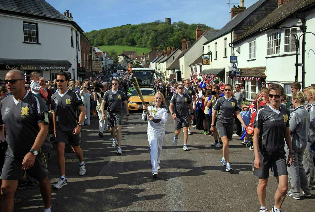 MINEHEAD, ENGLAND - MAY 21: Olympic torchbearer Katrina Doyle runs with the Olympic flame through Dunster on May 21, 2012 near Minehead, England. The Olympic Flame arrived in the UK last Friday and is on the first leg of a 70-day relay involving 8,000 torchbearers covering 8,000 miles. (Photo by Matt Cardy/Getty Images)