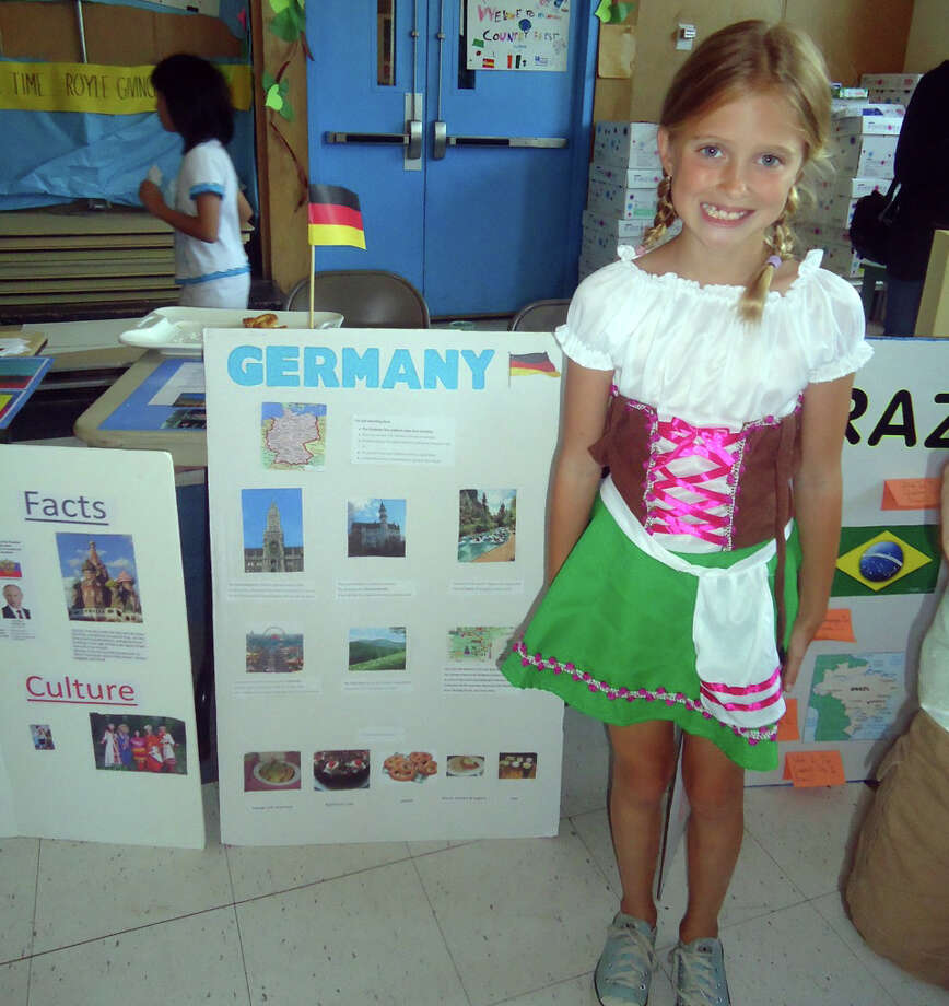 Lindsay Arrix dons a dirndl and stands in front of the poster she made about Germany at Royle School in Darien, Conn. Photo: Contributed Photo