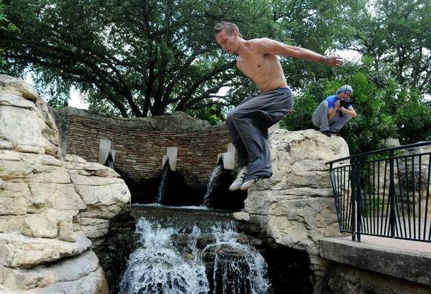 Mike Avery jumps over a water fall by the Henry B. Gonzalez convention center in San Antonio on Friday, June 8, 2012. Photo: Billy Calzada, San Antonio Express-News / © 2012 San Antonio Express-News