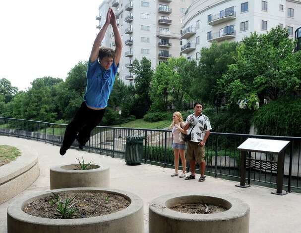 Dillon Gates of the group Parkour San Antonio jumps over planters as people strolling on the river watch near the Nueva Street Dam in downtown San Antonio on Friday, June 8, 2012. Photo: Billy Calzada, San Antonio Express-News / © 2012 San Antonio Express-News