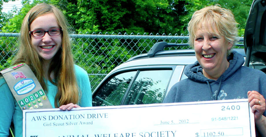 For her Girl Scout Silver Award project, Katie Polley of New Milford recently organized a district-wide drive to collect needed supplies for the Animal Welfare Society. Katie is shown here presenting the items collected and a check for more than $1,000 to AWS manager Renee Gardner. June 2012  Courtesy of the Polley family Photo: Contributed Photo