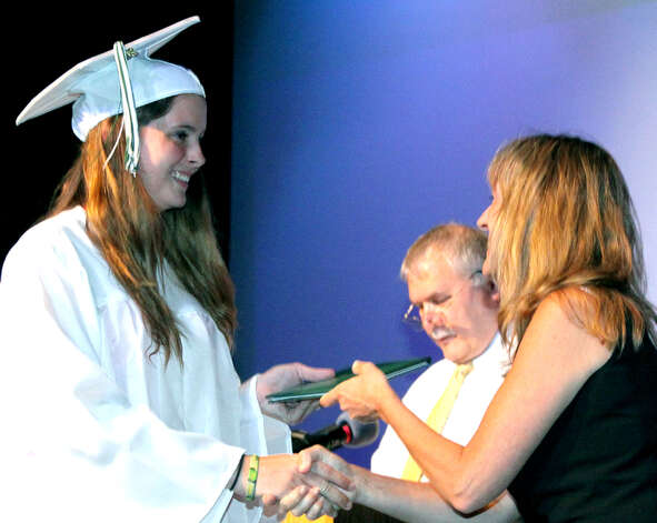 Program director Denise Duggan presents a Class of 2012 diploma to new graduate Amber Varley during the New Milford adult education graduation exercises. Adult education guidance counselor Joe Neff is seen reading the roll of graduates. June 13, 2012 Photo: Walter Kidd