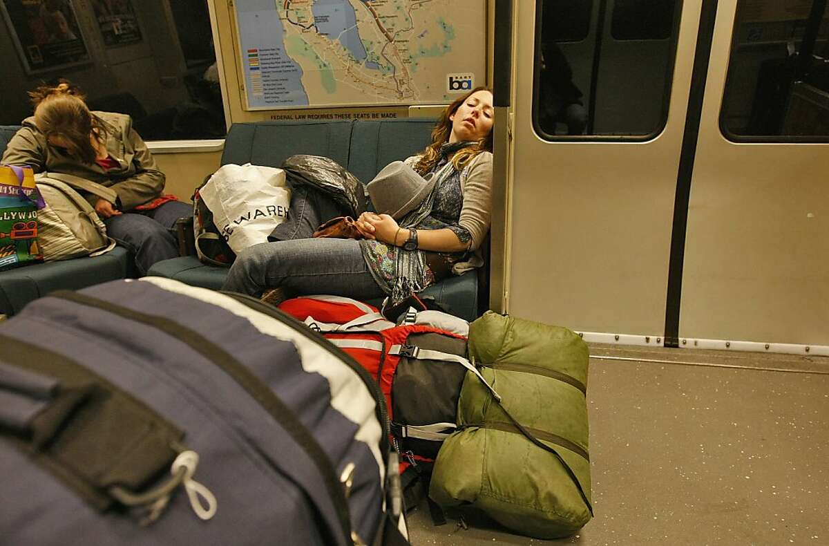 Travelers Stephanie McGrory sleeps as she rides BART to San Francisco from the International Airport, Thursday May 28, 2009, in San Francisco, Calif.