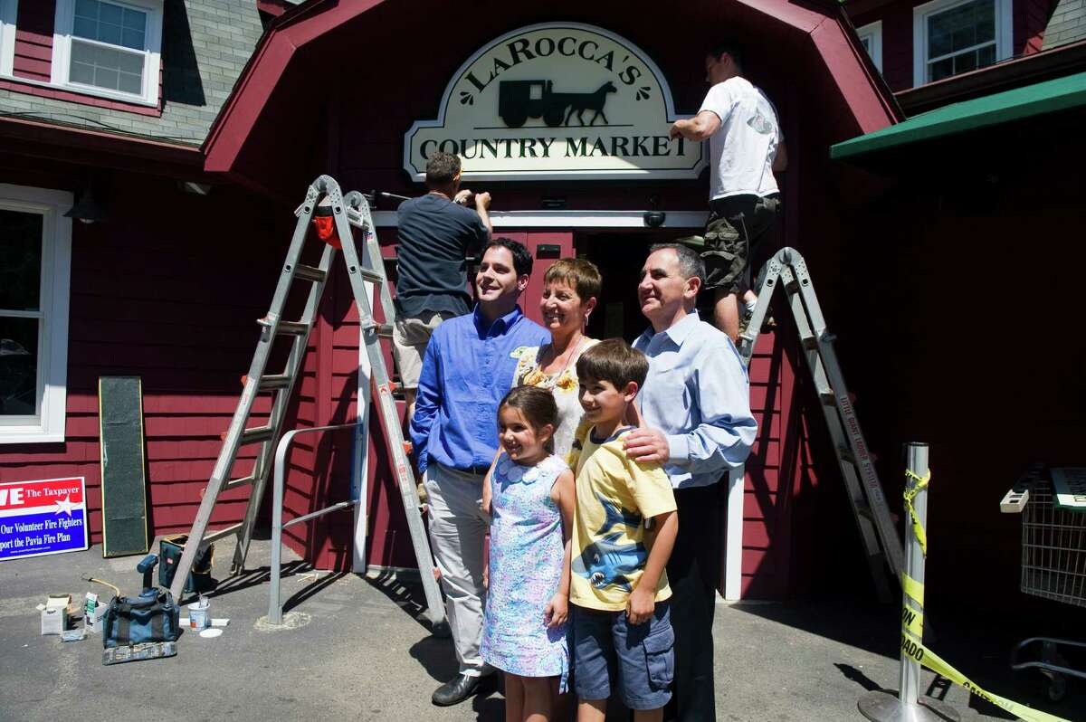 The Larocca family poses for a photo as the new sign is hung at LaRocca's Country Market, previously Giovanni's Country Market, on Old Long Ridge Road in Stamford, Conn., June 27, 2012. Tommy LaRocca, left, owns the store, his parents, Tommaso and Lucy, join him for the sign hanging and his niece and nephew Anna and Gabriel Maiolo. LaRocca bought the market from his family two years ago and renovated the space to allow for broader aisles and a 40 foot gourmet counter. LaRocca's is now energy efficient and is stocked with more than a third of the products coming from local sources. The market is holding a grand opening Saturday June 30.