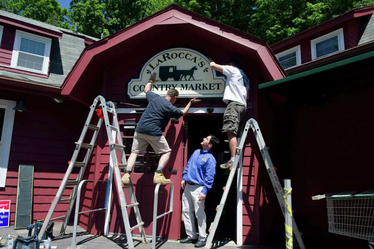 Tommy LaRocca watches as the new sign is hung at LaRocca's Country Market, previously Giovanni's Country Market, on Old Long Ridge Road in Stamford, Conn., June 27, 2012. The sign, which was hand carved by New England Sign Carvers, is hung by Steve Sutton, left, and Matt Hryniewicz. LaRocca bought the market from his family two years ago and renovated the space to allow for broader aisles and a 40 foot gourmet counter. LaRocca's is now energy efficient and is stocked with more than a third of the products coming from local sources. The market is holding a grand opening Saturday June 30.