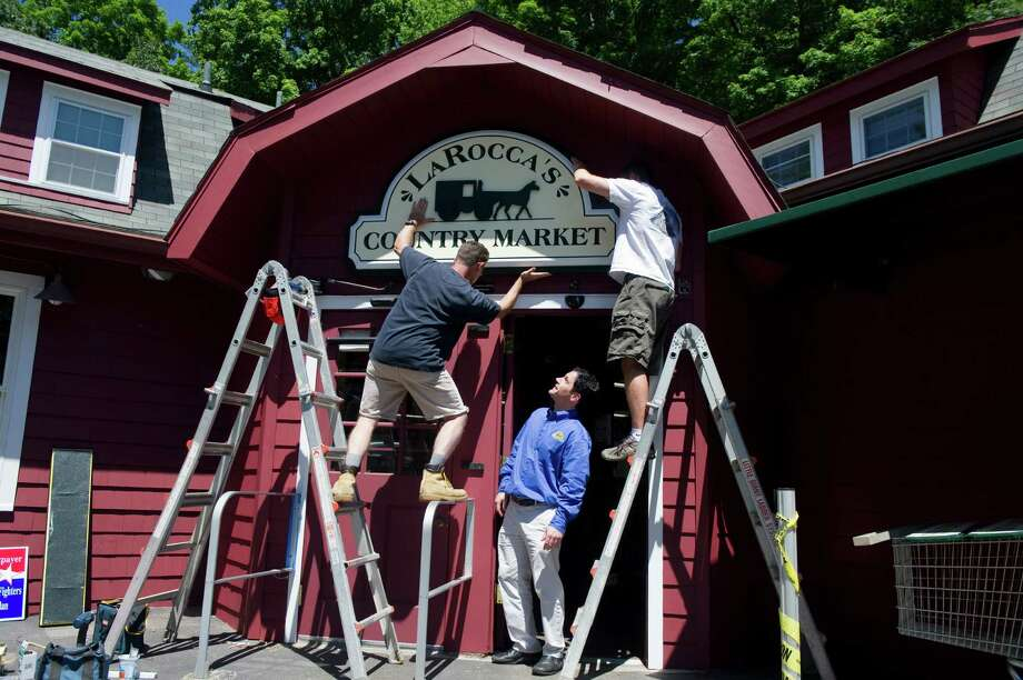 Tommy LaRocca watches as the new sign is hung at LaRocca's Country Market, previously Giovanni's Country Market, on Old Long Ridge Road in Stamford, Conn., June 27, 2012. The sign, which was hand carved by New England Sign Carvers, is hung by Steve Sutton, left, and Matt Hryniewicz. LaRocca bought the market from his family two years ago and renovated the space to allow for broader aisles and a 40 foot gourmet counter. LaRocca's is now energy efficient and is stocked with more than a third of the products coming from local sources. The market is holding a grand opening Saturday June 30. Photo: Keelin Daly / Stamford Advocate