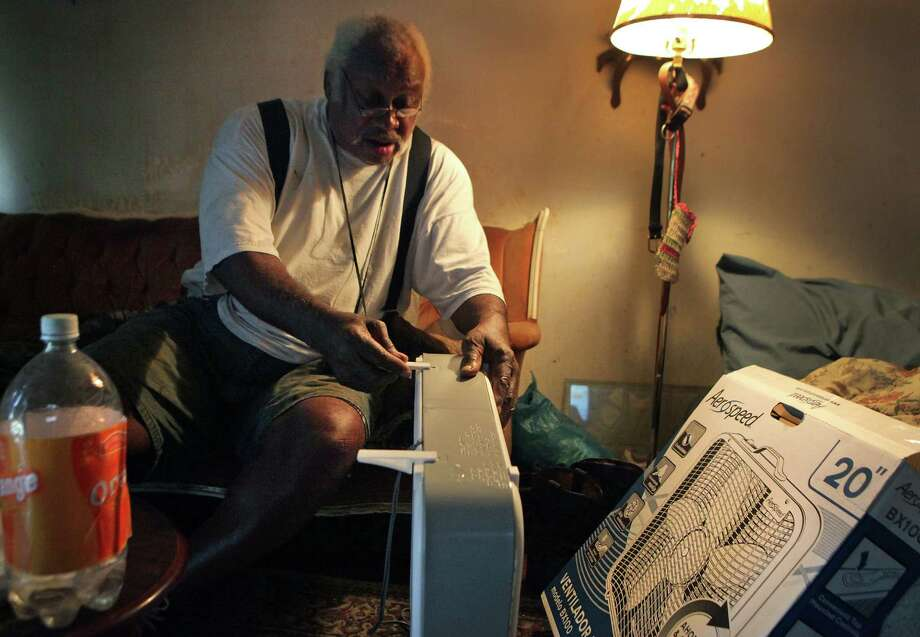 "After making three stops in his quest, Charles W. Stone finally gets to put a new 20"" box fan to work in his hot home. ""I'm burning up,"" he'd said. ""I need a fan."" Photo: Bob Owen, San Antonio Express-News / © 2012 San Antonio Express-News"