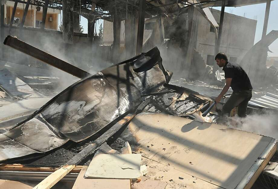 """In this photo released by the Syrian official news agency, SANA, a Syrian man stands inside a burnt room of al-Ikhbariya TV station which was destroyed after being attacked by gunmen, in the town of Drousha, about 20 kilometers (14 miles) south of Damascus, Syria, Wednesday, June 27, 2012. Gunmen raided the headquarters of a pro-government Syrian TV station early Wednesday, demolishing the building and killing several employees, the state media reported. Syrian officials denounced what they called a rebel """"massacre against the freedom of the press."""" (AP Photo/SANA) Photo: Hopd, Associated Press"""