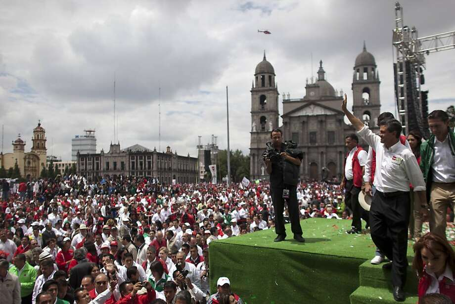 Presidential candidate Enrique Pena Nieto, right, of the Institutional Revolutionary Party (PRI), waves to supporters during his closing campaign rally in Toluca, Mexico, Wednesday, June 27, 2012. Mexico will hold its presidential election on Sunday. (AP Photo/Alexandre Meneghini) Photo: Alexandre Meneghini, Associated Press