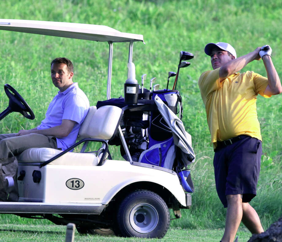 Michael Retter, a member at Lake Waramaug Country Club, follows through on one of 1,385 strokes he took June 19 during his fundraising golf marathon. Keeping him company is friend Brian Schmiedel.  Courtesy of Michael Retter Photo: Contributed Photo