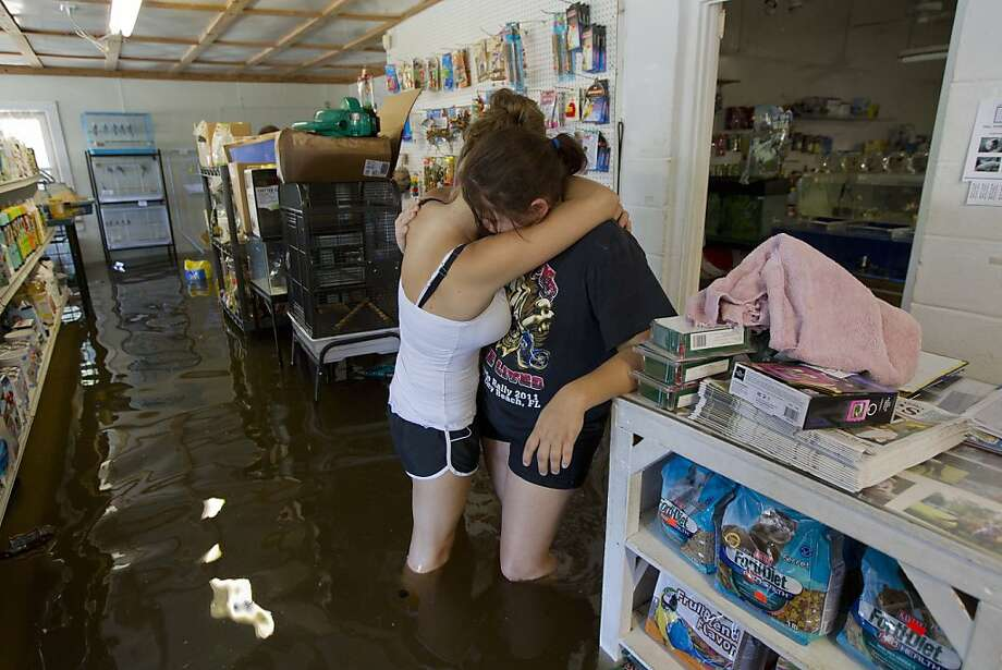 Tarra Piet, right, is embraced by her cousin Kursty Setty as they stand in Piet's fathers' flooded pet store Live Oak Fla., Wednesday, June 27, 2012. Dozens of homes and businesses were flooded by torrential rains from Tropical Storm Debby. (AP Photo/Dave Martin) Photo: Dave Martin, Associated Press