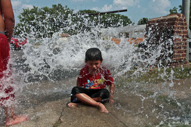 Josiah Castillo, 6, plays in the water flowing from a hydrant being flushed and tested by San Antonio Water System on a cul-de-sac in San Antonio on Wednesday, June 27, 2012. Photo: Lisa Krantz, San Antonio Express-News / © 2012 San Antonio Express-News