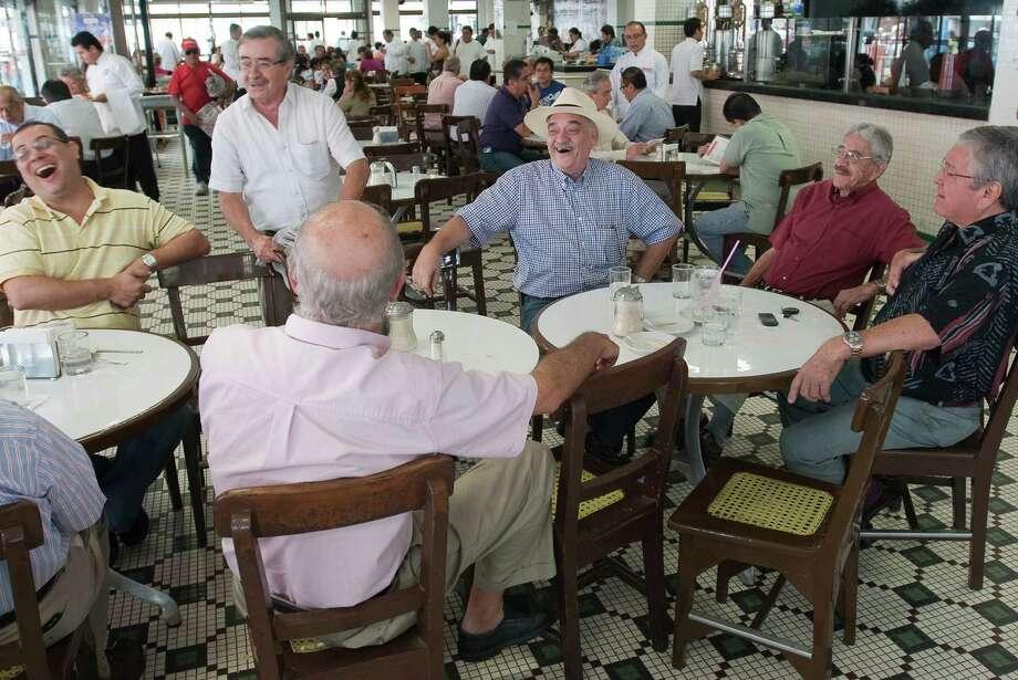 José Luis Sáenz Escalera, in hat, leads the way as politics dominates the conversation at the Cafe La Parroquia in Veracruz. Photo: Keith Dannemiller / ©2012 Keith Dannemiller