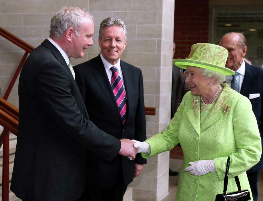Britain's Queen Elizabeth II shakes hands with Northern Ireland Deputy First Minister and former IRA commander Martin McGuinness watched by First minister Peter Robinson, centre, at the Lyric Theatre in Belfast, Northern Ireland, Wednesday, June 27, 2012. Photo: Paul Faith, Associated Press / POOL PA