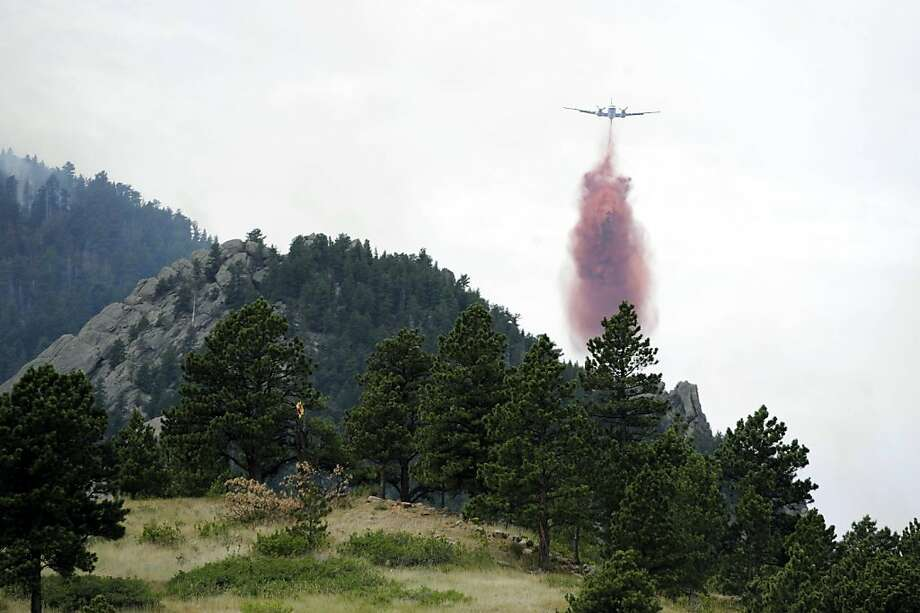 A tanker drops retardant near Bear Peak while battling a blaze on Wednesday, June 27, 2012, near Boulder, Colo. A Boulder fire and police spokeswoman said a wildfire burning west of Boulder is now within a mile and a half of the city, and fire managers are competing for resources as three major wildfires continue to burn in Colorado. (AP Photo/The Denver Post, Andy Cross) MAGS OUT; TV OUT; INTERNET OUT Photo: Andy Cross, Associated Press