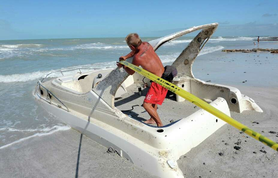 Manatee County Marine Rescue lifeguard Curtis McFee tapes off the area surrounding a boat Wednesday,