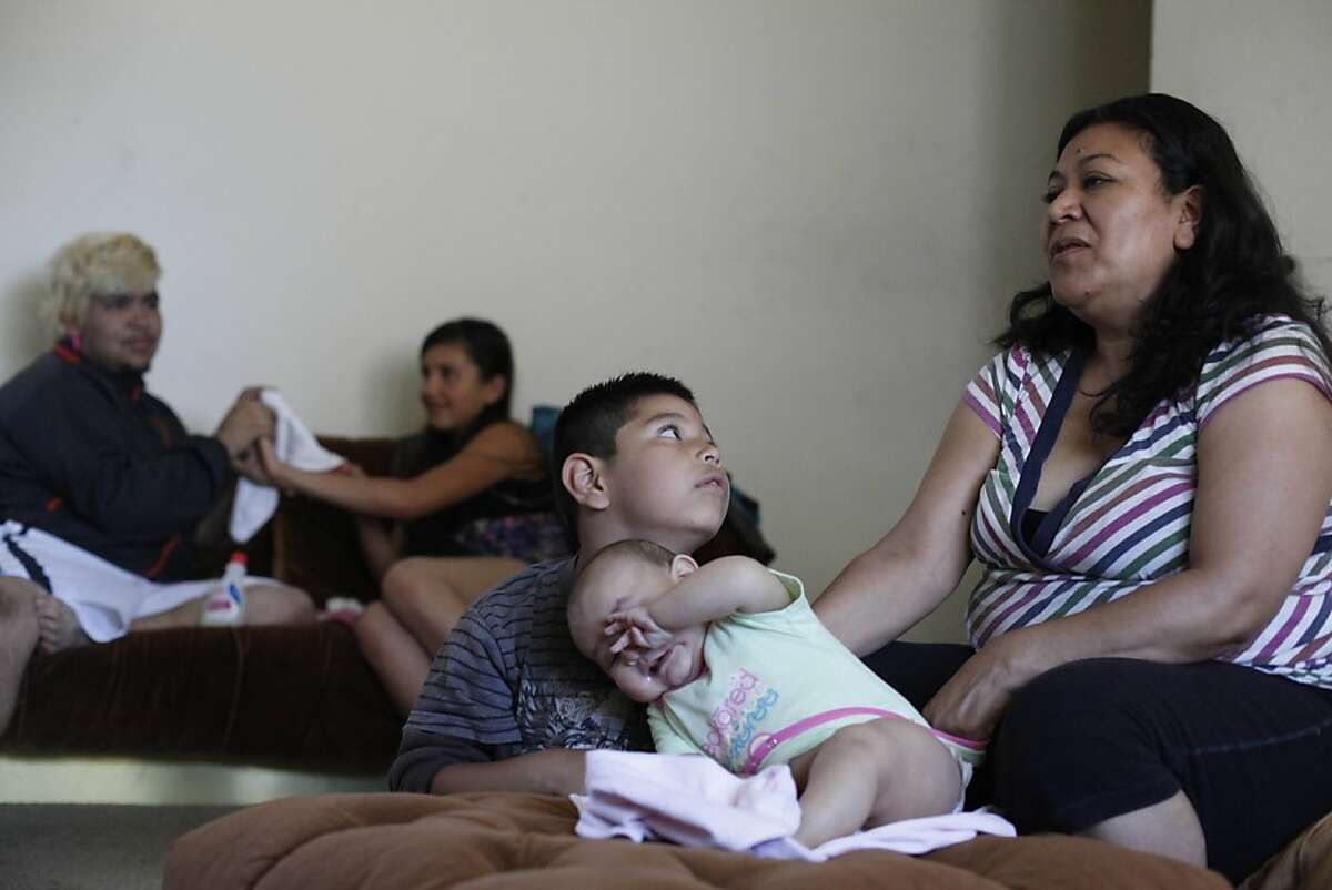 Diego Jimenez-Mota (center), 7, talks with his mother Macrina Mota Pineda (left) as they relax at home with their family on Wednesday, June 27, 2012 in San Mateo, Calif. Six of seven of Mota's children were previously on Healthy Families but are now on Medi-Cal but Mota Pineda prefers Healthy Families to Medi-Cal. Healthy Families is a low cost insurance for children and teens.
