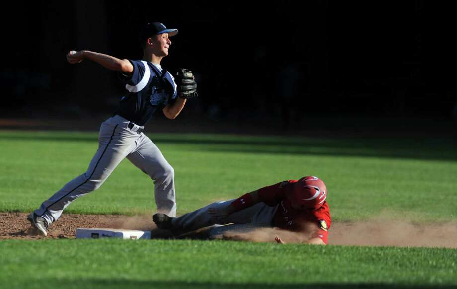 Stamford's Mike Palomba throws to first for a double play as Fairfield's Jay Sullivan slides to second Wednesday, June 27, 2012 during their American Legion baseball game at Owen Fish Park in Fairfield, Conn. Photo: Autumn Driscoll / Connecticut Post