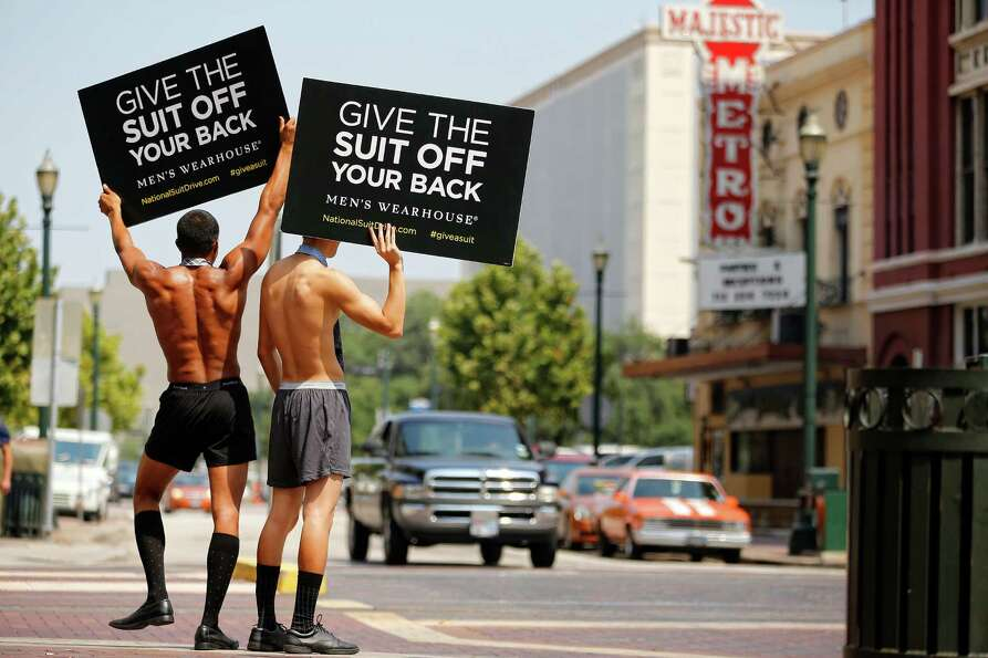 Models Michael Spinks, left, and Aisen Li, hold up signs promoting Men's Warehouse's charity suit dr