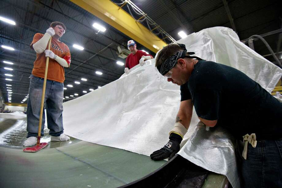 Employees Dillon Schultz, left, and Kyle Brow, center, watch as Randy Allen makes an adjustment to a layer of fiberglass fabric in a wind turbine blade mold made for General Electric Co.'s renewable energy business at TPI Composites Inc.'s manufacturing facility in Newton, Iowa, U.S., on Friday, June 22, 2012. The U.S. Census Bureau is scheduled to release durable goods data on June 27. Photographer: Daniel Acker/Bloomberg *** Local Caption *** Dillon Schultz; Kyle Brown; Randy Allen Photo: Daniel Acker, Bloomberg / © 2012 Bloomberg Finance LP
