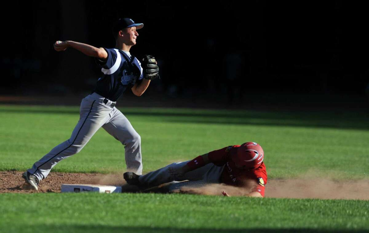 Stamford's Mike Palomba throws to first for a double play as Fairfield's Jay Sullivan slides to second Wednesday, June 27, 2012 during their American Legion baseball game at Owen Fish Park in Fairfield, Conn.
