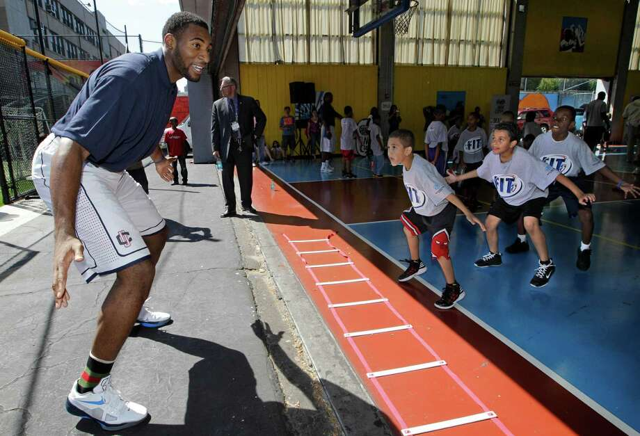NBA draft prospect Andre Drummond, left, leads Harlem youngsters through a drill during an NBA fitness clinic at the Children's Aid Society Dunlevy Milbank Boys & Girls Club in New York, Wednesday, June 27, 2012. The event was part of NBA FIT, the league's health and wellness program that encourages physical activity and healthy living for children and families. (AP Photo/Kathy Willens) Photo: Kathy Willens, Associated Press / AP